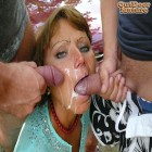 Matue slut sucking two cocks on a parkinglot