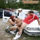 Red mature slut sucking cocks on a parking lot